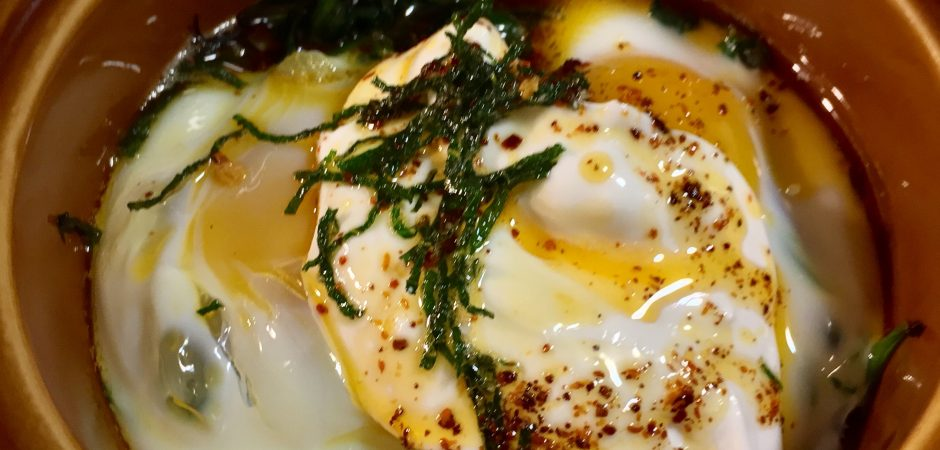 Baked Eggs on Hearty Greens with yogurt and chile photograph